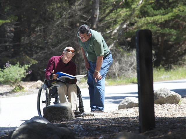 photo of docent helping a visitor in a wheelchair